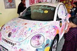 車体に応援メッセージを書く子ども=三木市福井