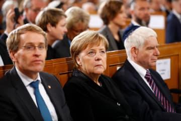 9日、ベルリンのシナゴーグで、ユダヤ人が襲われた「水晶の夜」の追悼式典に出席するメルケル首相(中央)(ロイター=共同)