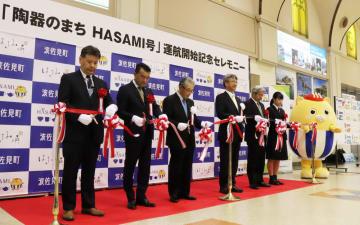 テープカットし、HASAMI号の就航を祝う関係者=長崎空港