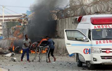 9日、爆発があった現場から負傷者を搬送する救急隊員=ソマリア・モガディシオ(ロイター=共同)