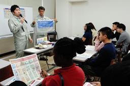来日したばかりの留学生らにごみ出しルールを伝える市環境局職員=兵庫区浜崎通3