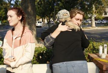 乱射があった米ロサンゼルス郊外のバー付近で抱き合う生存者と家族ら=9日(AP=共同)