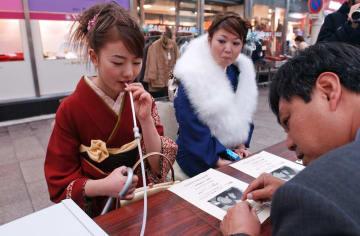 長崎市歯科医師会の口臭測定を受ける新成人ら=長崎市浜町、浜町アーケード