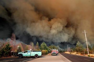 8日、米カリフォルニア州の山火事現場から立ち上る黒煙(ゲッティ=共同)