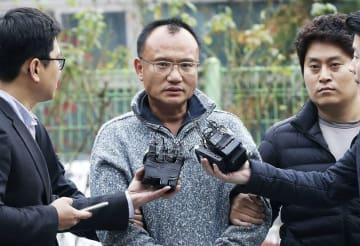 暴行容疑などで拘束された後、記者の取材に応じるIT企業会長のヤン・ジンホ容疑者(中央)=7日、韓国・水原(聯合=共同)