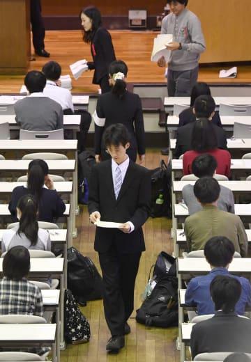大学入学共通テストの本番を想定したリハーサルで、問題を配る大学関係者=10日午前、東京都目黒区の東大駒場キャンパス