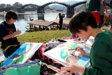 真剣な表情で錦帯橋を描く参加者
