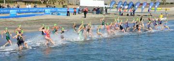 水しぶきを上げながら、一斉に海へ駆け出すトライアスロンW杯「エリート」部門の女子選手ら=10日午前、宮崎市・サンビーチ一ツ葉