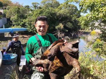 「緊急SOS!池の水ぜんぶ抜く大作戦 3時間半SP」でワニガメを捕獲した的場浩司さん=テレビ東京提供