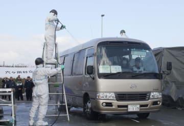 東北電力東通原発の炉心損傷を想定した訓練で、避難住民を乗せたバスを除染する陸上自衛隊員=11日午前、青森県六ケ所村