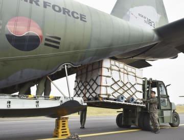 11日、北朝鮮に送るミカンを輸送機に積む韓国軍関係者=韓国・済州(韓国国防省提供・共同)