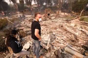 全焼した住宅を見る人たち=10日、米カリフォルニア州マリブ(AP=共同)