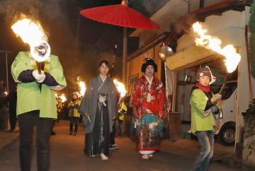 男性が花嫁に、女性が花婿に扮して練り歩く伝統行事「むじなのむかさり」=11日夜、山形県村山市