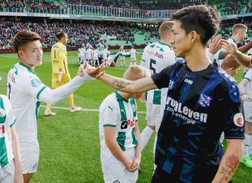 試合前、握手を交わすフローニンゲンの堂安(左)とヘーレンフェインの小林=フローニンゲン(共同)