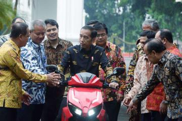 国産電動スクーター「GESITS(グシッツ)」を試乗するジョコ大統領(中央、写真は内閣官房提供)