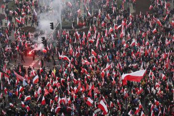 11日、ポーランドの首都ワルシャワで、同国の独立回復100年を記念し、炎を燃やし、国旗を掲げて行進する人々(ゲッティ=共同)
