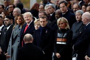 11日、パリの凱旋門の式典会場に到着したロシアのプーチン大統領(手前)やフランスのマクロン大統領(中央)、トランプ米大統領(左から3人目)ら(ロイター=共同)