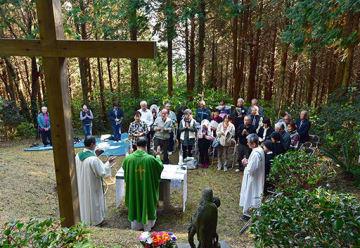 崎津と大江両教会の信徒らが参列し、根引山の木立の中で開かれたミサ=11日午後、天草市河浦町