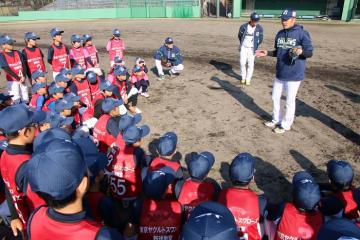 小学生に投球の基本動作を指導する近藤投手(右)=五島市中央公園野球場