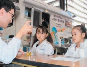 白衣を着て、薬剤師の仕事を体験する子どもたち