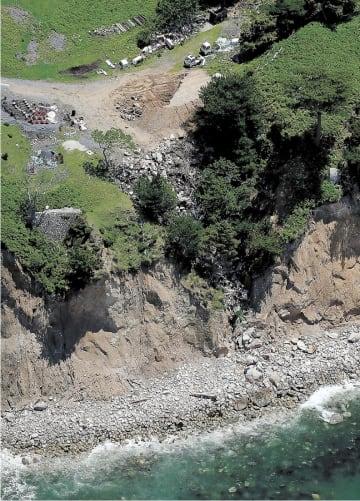 投棄現場の崖(写真中央)。海岸線(右下)近くまで廃棄物が堆積していた=5月下旬、石巻市の金華山