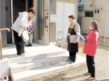 お年寄り(奥)の家を訪問する会員ら