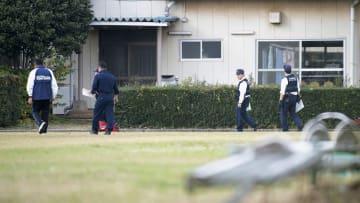 千葉県立八街高校のグラウンド付近を調べる警察官ら=12日午後1時7分、千葉県八街市
