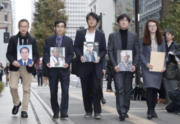韓国人元徴用工らの写真を手に新日鉄住金本社を訪れる原告の弁護士ら=12日午前、東京都千代田区