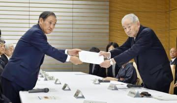 拉致問題相を兼務する菅官房長官(左)に要請書を手渡す特定失踪者家族会の大沢昭一会長=12日午後、首相官邸