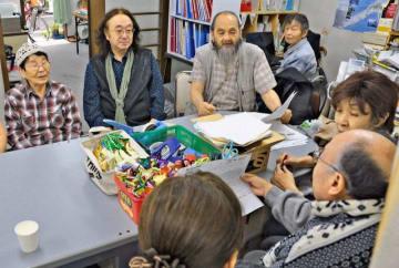 ペルー出身の男性(手前中央)から相談を受ける神奈川シティユニオンの村山執行委員長(左から2人目)ら=9日、川崎市幸区
