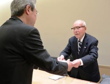 申請書を黒川館長に手渡す森さん(右)=長崎市、国立長崎原爆死没者追悼平和祈念館
