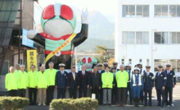 4年ぶりに塗り替えられた仮面ライダー像と玖珠ライオンズクラブの会員ら=玖珠町