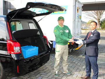 ダイレクトメールを乗合タクシーのトランクに積み、ヤマト運輸の従業員から端末を受け取る高富タクシーの関係者=12日午前、山県市役所