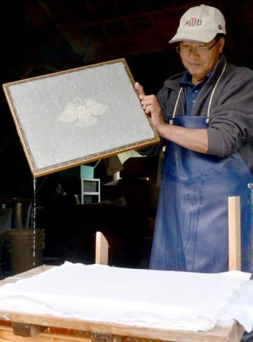 多良木高の卒業証書の和紙を作る椎葉袈史さん。紙の中央に同校の校章の透かしが入っている=多良木町
