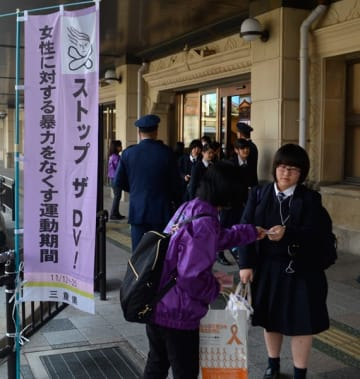 【DV相談啓発用のティッシュを受け取る女性(右)=伊勢市岩渕2丁目で】
