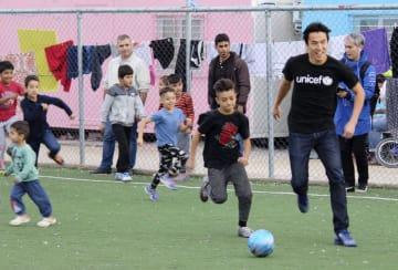 アテネの難民キャンプで、子供たちとボールを追う長谷部誠選手(右端)=12日(共同)