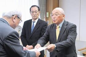 菊谷市長に答申書を手渡す渡邉会長(右)ら