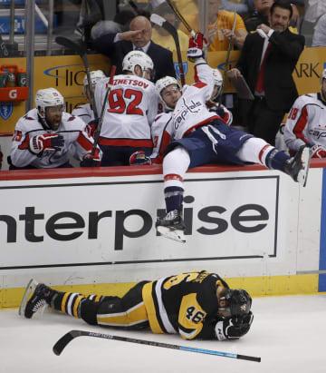 試合中の激しい衝突で頭を抱えて倒れ込むペンギンズの選手とベンチまで吹き飛ばされたキャピタルズの選手=5月、ピッツバーグ(AP=共同)