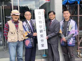北大総合博物館の分室開設で、プレートを掲げる(左から)堀田さん、竹中町長、中川館長、小林准教授