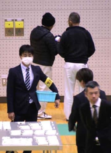 竹原市議選の開票作業中に投票の束の近くでスマートフォンを操作する立会人(奥)11日午後9時