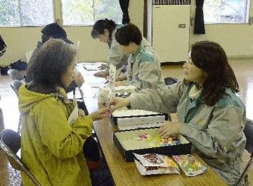 青森県内で初めて実施された安定ヨウ素剤緊急配布訓練。自治体職員が簡易問診票を確認し、薬剤に見立てたラムネ菓子を住民に手渡した=11日、東通村の石持地区活力倍増センター
