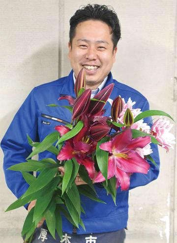 濃いえんじ色のボンバスティックと八重咲きのサマンサを手にする三浦さん