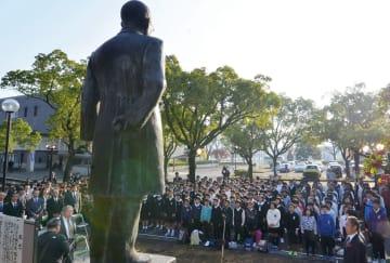 犬童球渓の銅像を前に歌う小学生ら=人吉市