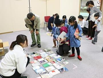 【読みたい本がないか、床に並んだ出品本を見る参加者(和歌山県みなべ町芝で)】