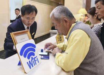 平壌市内のホテルのフロントでWi―Fiサービスの説明を受ける福岡県日朝友好協会訪問団のメンバー=10月24日(共同)