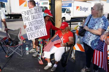 12日、米フロリダ州ブロワード郡で再集計に抗議し座り込む人々(ロイター=共同)