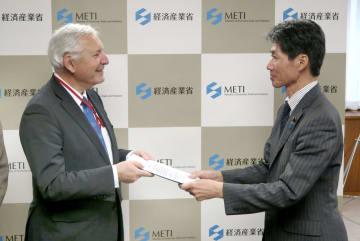 磯崎仁彦経産副大臣(右)に報告書案を手渡すIAEA調査団のクリストフ・グゼリ団長=13日、経産省