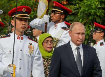 ロシアのプーチン大統領(右)とシンガポールのハリマ大統領(中央)=13日、シンガポールの大統領官邸(タス=共同)