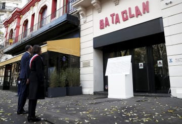13日、パリ同時多発テロの現場となったバタクラン劇場前での追悼式典に出席したフランスのフィリップ首相(左)ら(ロイター=共同)