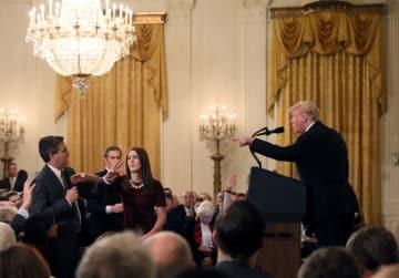 ホワイトハウスの記者会見で、トランプ大統領(右)に質問するCNN記者(左)のマイクを取ろうと手を伸ばす女性スタッフ=7日、米ワシントン(ロイター=共同)